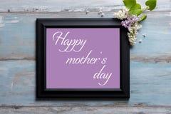 与淡紫色花的画框和在蓝色背景的愉快的母亲` s天消息 库存图片