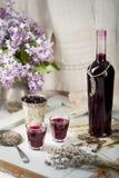 与淡紫色花的黑醋栗自创酒 木背景 库存图片
