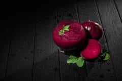 与深红色的鸡尾酒的一块点心玻璃在黑背景 健康奶昔用甜菜根、薄菏和糖 复制 库存照片
