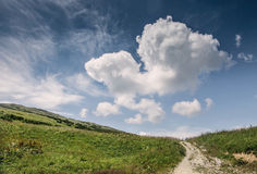 与深蓝天和大云彩的小山风景 免版税库存图片