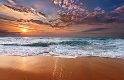 与深蓝天的五颜六色的海洋海滩日出 免版税库存图片