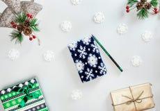 与深蓝笔记本、小绿色箱子、铅笔、雪花和云杉的分支红色莓果的圣诞节构成 免版税库存图片