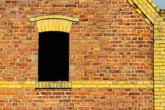 与深黑色内部的开窗口在有葡萄酒老谷仓或仓库的黄色细节的脏的红砖墙壁上 免版税库存图片