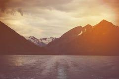 与深黑色湖和高峭壁的阴沉的风景 库存图片