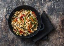 与混乱的一平底锅yaki乌龙面面条油煎菜 素食面条用青豆,甜椒,蘑菇,红萝卜- healt 免版税库存照片