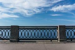 与混凝土桩的锻铁栏杆反对与云彩的蓝天 免版税库存图片