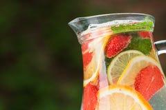 与混合茶点鸡尾酒的玻璃水瓶 免版税库存图片