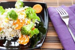 与混合蔬菜的煮沸的米在黑色盘 免版税库存图片