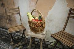 与混杂的有机菜的柳条筐在木椅子 免版税库存图片