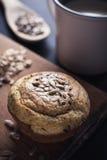 与混杂的种子和杯子的新鲜的松饼在背景中 库存图片