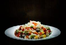 与混杂的菜的米在黑暗的木背景的白色板材 免版税图库摄影