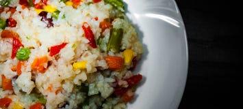 与混杂的菜的米在黑暗的木背景的白色板材 免版税库存照片