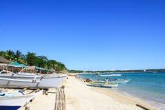 与清楚的蓝天、水和游船的白色沙子海滩 免版税图库摄影