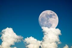 与清楚的蓝天云彩白天的超级满月为背景背景使用 库存图片