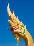 与清楚的蓝天, Udonthani,泰国的金黄纳卡人雕象 免版税库存照片