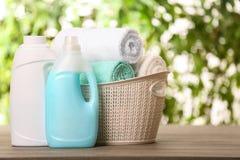 与清洁毛巾和洗涤剂的篮子在反对被弄脏的背景的桌上 免版税图库摄影