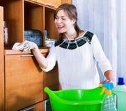 与清洁剂的愉快的成人深色的打扫灰尘 免版税库存图片