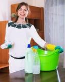 与清洁剂的年轻美丽的成人深色的打扫灰尘 免版税库存图片