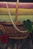 与清洁毛巾五颜六色的红色花和绿色叶子的篮子在木背景减速火箭的过滤器 免版税库存图片