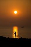 与渔夫和一艘小驳船,考尔莱,意大利的日出, 库存照片