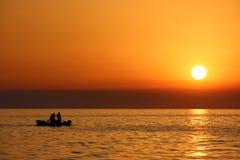 与渔夫` s剪影的橙色日落 免版税库存图片