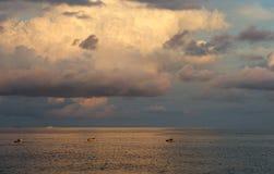 与渔船和云彩形成在金黄日落小时,温暖的晚上光,风景的美好的海视图 图库摄影