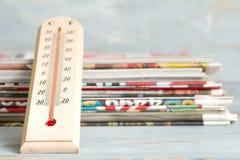 与温度计和报纸的最新新闻创造性的标志 库存图片