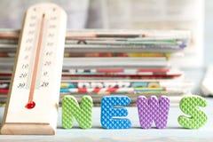 与温度计和报纸的最新新闻创造性的标志 免版税库存图片