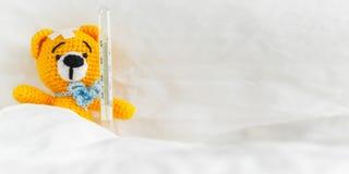 与温度计和膏药的黄色玩具熊在头在白色卧室 钞票 免版税库存图片