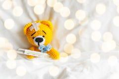 与温度计和膏药的黄色玩具熊在头在白色卧室 免版税库存照片