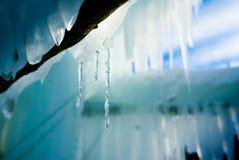 与温暖的光反射的温暖的宜人的冰柱背景 免版税库存照片