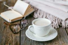 与温暖的格子花呢披肩书和热的奶茶的秋天晚上 库存照片