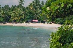 与游人和地方渔夫的海洋风景与棕榈树的沙滩的 图库摄影