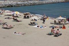 与游人和本机的拥挤海滩s的 库存照片