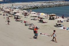 与游人和本机的拥挤海滩s的 免版税库存照片