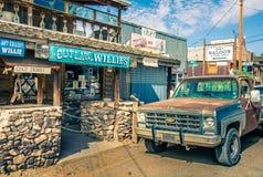 与游人商店和老生锈的提取汽车的现代狂放的西部风景在Oatman 库存图片