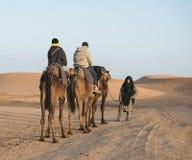 与游人夫妇的阿拉伯指南在撒哈拉大沙漠 免版税库存图片