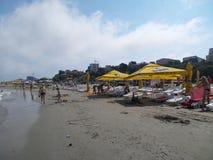 与游人晒黑和伞的海滩视图 图库摄影
