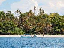 与游人的小船游览一个热带海滩的 免版税库存照片