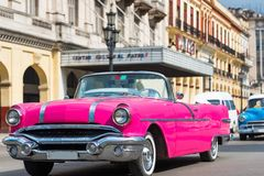 与游人的美国桃红色敞篷车比德经典汽车驱动通过哈瓦那古巴- Serie古巴报告文学 库存图片