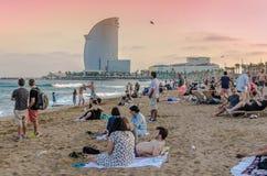 与游人的巴塞罗那海滩日落的 免版税库存照片