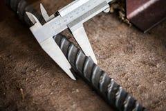与游标卡尺的测量的被扭屈的棒钢 免版税库存照片