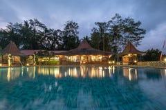 与游泳场的Banyuwangi,印度尼西亚-建筑学木手段巴厘岛在黄昏的样式和照明 免版税库存图片
