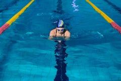 与游泳帽子的妇女游泳在游泳池 免版税库存图片