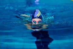 与游泳帽子的妇女游泳在游泳池 免版税库存照片