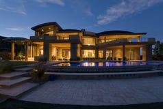 与游泳池的现代大厦在黄昏 免版税库存图片