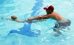 与游泳辅导员的小男孩游泳 免版税库存图片