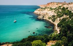与游艇、岩石和绿叶的美丽的海景海湾 免版税库存照片