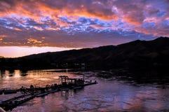 与湖、天空反射、小船和山麓小丘剪影的剧烈的日落风景 边界的斯内克河爱达荷和洗涤 图库摄影