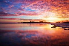 与湖和日落火热的天空的冬天风景。 库存照片